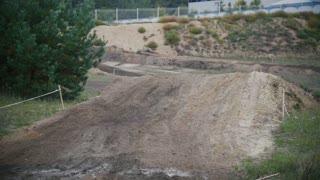Motocross racer mxgirl on dirt bike jumping on track in rapid shoot, close up, Slow motion