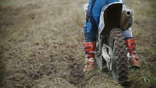 Motocross racer start riding his dirt Cross MX bike kicking up dust rear view, slow motion