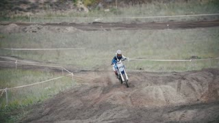 Motocross rider in a red jumpsuit chasing racer mxgirl on dirt bike on track in rapid shoot, Slow motion, close up