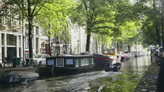 Motor boat sails in Amstel canal. Amsterdam, Holland, The Netherlands.