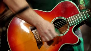 Musician at rock concert - guitarists plays acoustic guitar in night club