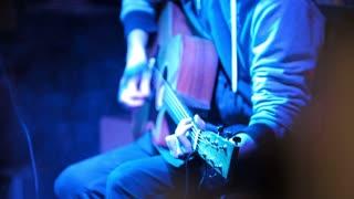Musician in night club guitarist plays acoustic guitar, close up