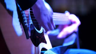 Musician in night club - guitarist plays blues acoustic guitar, extremely close up