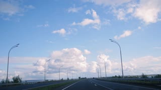 Open road with clouds and blue sky, day highway with lights