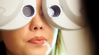 Ophthalmology clinic - woman checks vision by modern equipment - left eye