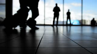 Passengers going to boarding with baggage in front of window in airport, silhouette