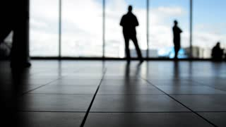 Passengers waiting to boarding in front of window in airport, silhouette