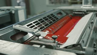 Polygraphy printing industry - red paint on ink roller, extremely close up