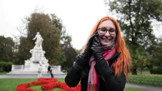 Pretty young woman with red hair and glasses emotionally talking on phone in park - Burggarten, Vienna
