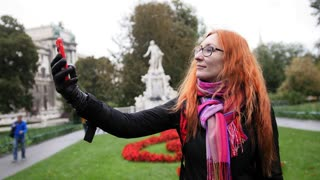 Pretty young woman with red hair and glasses making selfie in park - Burggarten, Vienna