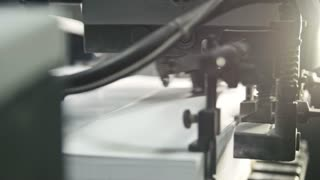 Printed sheets of paper are served in the printing press. Offset printing, CMYK, close up