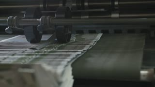 Printing Process on polygraph industry - brochures moving on the conveyor belt, extremely close up