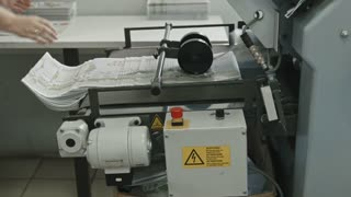 Printing Process on polygraph industry - female hands collect brochures from the conveyor belt