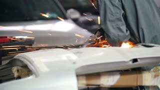 Professional car service - worker grinding metal with a circular saw, rear view