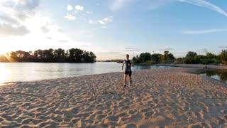 Road runner man running on the beach at dusk, slow-motion