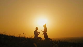 Romantic Silhouette of Man Getting Down on his Knee and Proposing to Woman on high hill - Couple Gets Engaged at Sunset - Man Putting Ring on Girl's Finger, slow motion