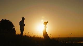 Romantic Silhouette of Man Getting Down on his Knee and Proposing to Woman on high hill - Couple Gets Engaged at Sunset - Man Putting Ring on Girl's Finger