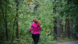 Runner young woman running in autumn park exercising outdoors at rain, pink training suit, rear view, slow motion
