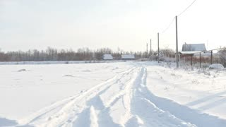 Russian village - snow-covered winter road at sunny day