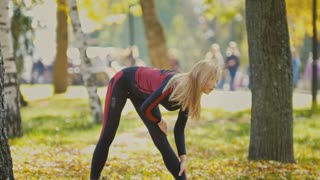 Sexy Attractive female blonde bikini-fitness model stretching in the autumn park on ground covered yellow leaves - body flexibility