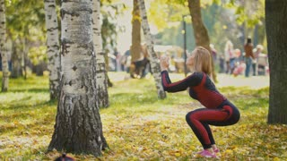 Sexy Attractive female blonde bikini-fitness model stretching in the autumn park on ground covered yellow leaves - exercises about the birch