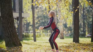 Sexy Attractive female blonde bikini-fitness model stretching in the autumn park on ground covered yellow leaves in slow motion