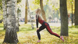 Sexy Attractive female blonde bikini-fitness model stretching in the autumn park on ground covered yellow leaves - leg extension