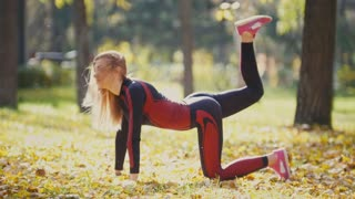 Sexy Attractive female blonde bikini-fitness model stretching in the autumn park on ground covered yellow leaves - leg lifts
