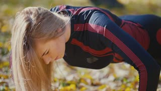 Sexy Attractive female blonde bikini-fitness model stretching in the autumn park on ground covered yellow leaves - pushups, close up