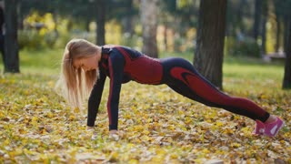 Sexy Attractive female blonde bikini-fitness model stretching in the autumn park on ground covered yellow leaves - pushups