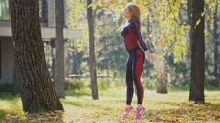 Sexy Attractive female blonde bikini-fitness model stretching in the autumn park on ground covered yellow leaves - sports squats