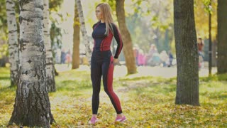 Sexy Attractive female blonde bikini-fitness model stretching in the autumn park on ground covered yellow leaves - stretching arms