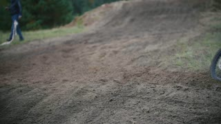 Slow motion: Motocross racer jumping. Rear view of biker on track in rapid shoot