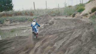 Slow motion: Motocross racer jumping. Rear view of biker on track