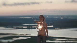Smiling young woman dancing on a high hill with sparkler at dusk