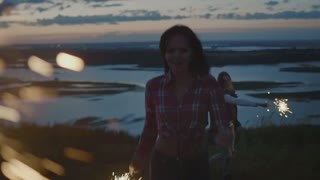 Smiling young woman dancing on a high hill with sparkler at sunset in slow motion