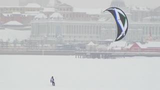 Snow-kite sportsmen sliding on ice river - winter extremal sport at blizzard