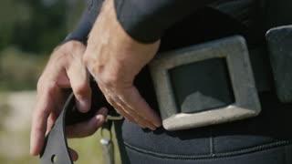 Spear underwater fisherman wearing belt with weights, preparing for hunt
