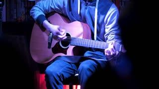 Spectators looks at guitarist plays acoustic guitar in night club, close up