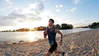 Strong male runner at the beach takes a break to get his breath back, slow-motion