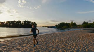 Strong male runner at the beach takes a break to get his breath back