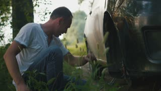 strong man repairing the wheel of a car in the woods