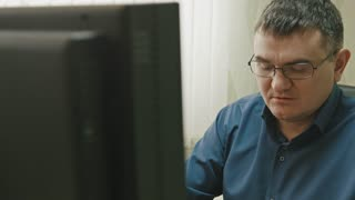Stuff in office: man in glasses working at computer, close up