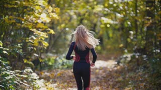 Sunny Autumn Jogging. Young active female athlete with white hair running outdoor in park. Healthy women, rear view, slow-motion