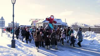 Sviyagsk, Russia - 26 February 2017: The pancake week - Russian ethnical carnival - Maslennica - Shrovetide - the crowd carries the effigy of winter to burn, snow sunny day