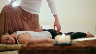 Thai massage - young woman gets Thai traditional therapy for shoulders, slider shot