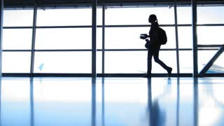 The girl with the backpack with glasses going in airport in front of window opposite the runway, silhouette