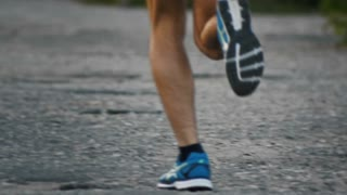 The legs of a runner running in park on asphalt at dusk, close-up, slow-motion