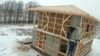 Time-lapse of construction house of straw bales. installing cladding panels on the wall on the second floor