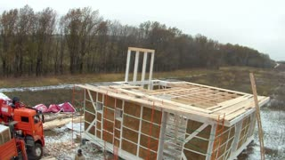 Time-lapse of construction house of straw bales . Truck unloads construction blocks for second floor